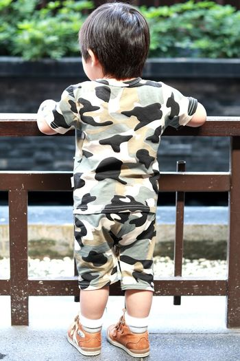 Rear View Of Baby Boy Standing By Railing