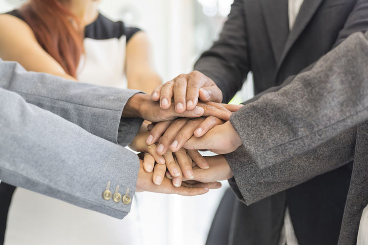 Midsection Of Businessmen Holding Hands