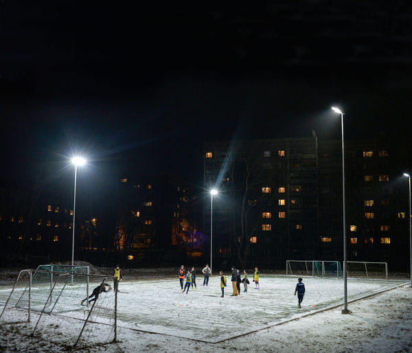Players practicing on soccer field in stadium at night
