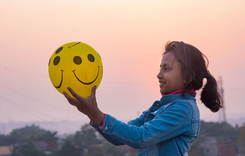 Girl holding balloon with smily printed against sky during sunset