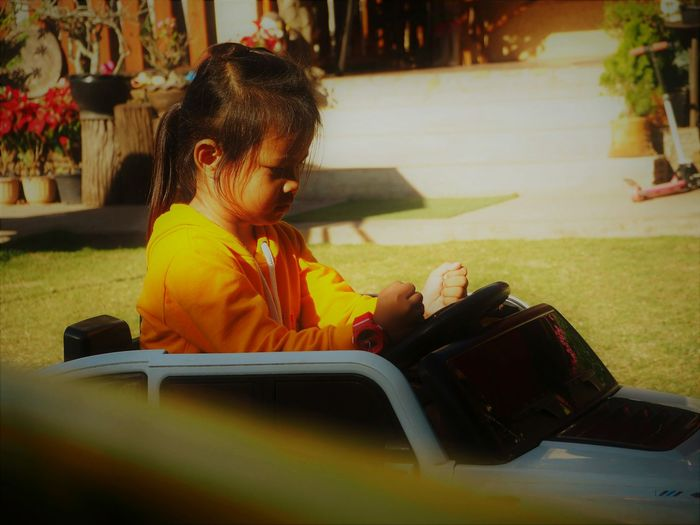 Side view of girl sitting in toy car at park