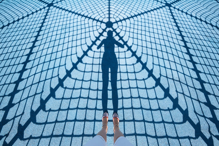 Low section of woman with shadow on footpath
