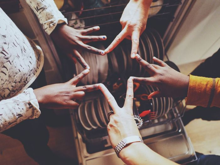 Cropped image of friends making star shape over dishwasher in kitchen