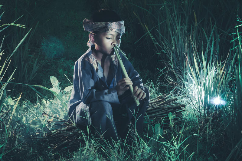 Boy Playing Flute On Field At Night