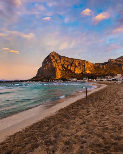 Water Sea Beach Land Sky Beauty In Nature Sand Scenics - Nature Cloud - Sky Rock Nature Tranquility Tranquil Scene Solid Rock - Object Incidental People Idyllic Mountain Sunset Outdoors