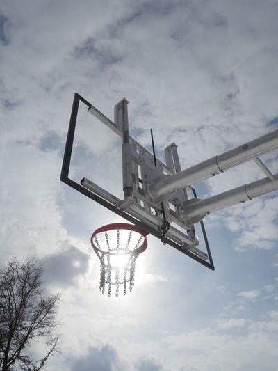 Optical illusion of sun in basketball hoop against sky