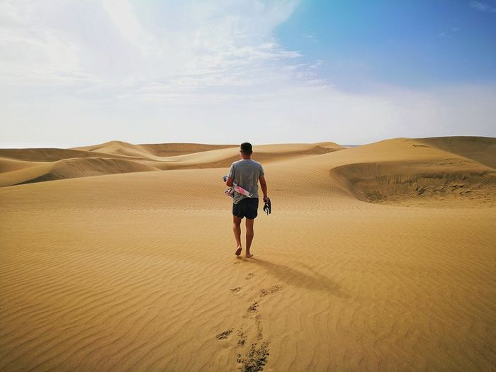 Full length rear view of man on desert
