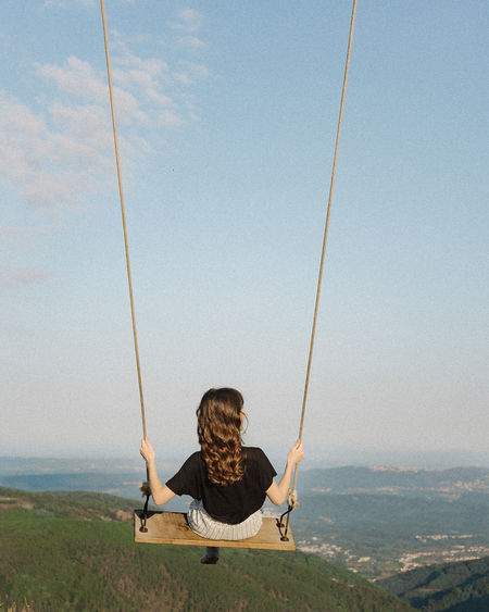 Rear view of woman sitting on swing against mountains