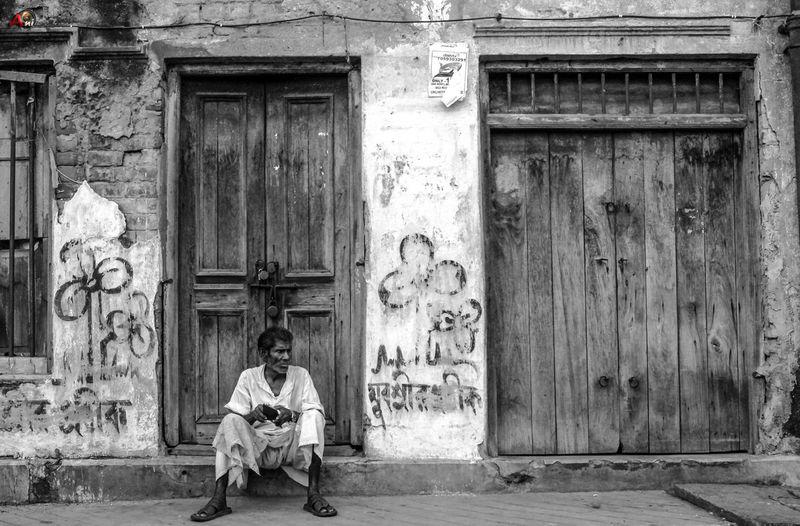Portrait of man sitting against door