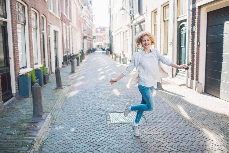 Cheerful woman walking on street in city