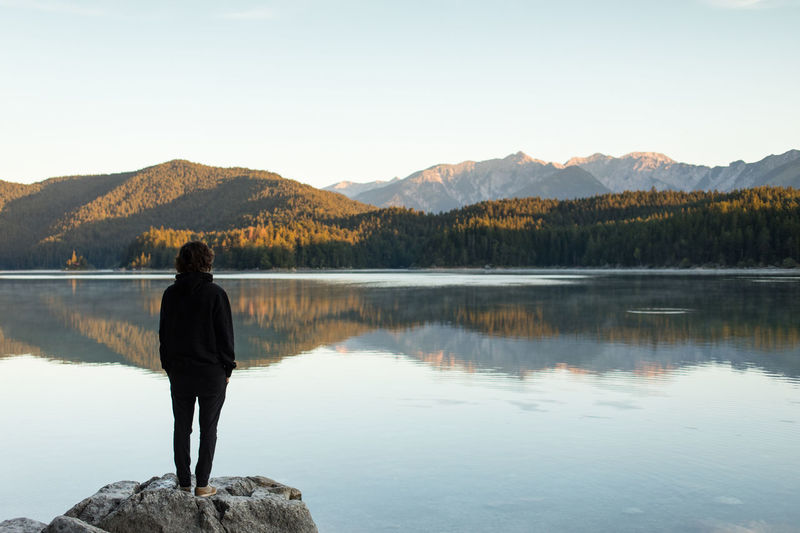 Rear view of woman looking at lake against clear sky
