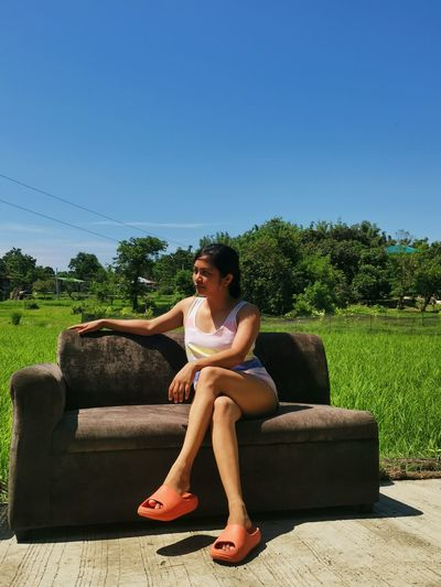 Full length of young woman sitting against blue sky