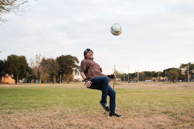 Man playing with ball on field against sky