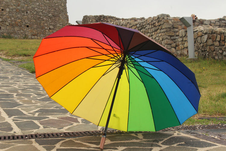 Colors Colourful Colours Rainbow Umbrella Architecture Close-up Colorful Day Focus On Foreground Footpath Land Multi Colored Nature No People Outdoors Parasol Pattern Protection Rain Rainbow Rainy Season Striped Umbrella Wall - Building Feature Yellow
