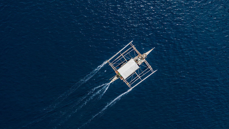 Aerial view of outrigger boat in sea