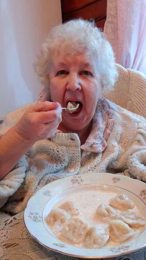 Portrait Of Senior Woman Eating Dumplings At Home
