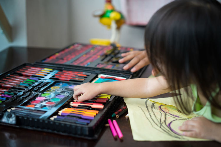 Close-up of girl coloring on table at home