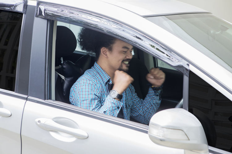 Businessman clenching fists in car