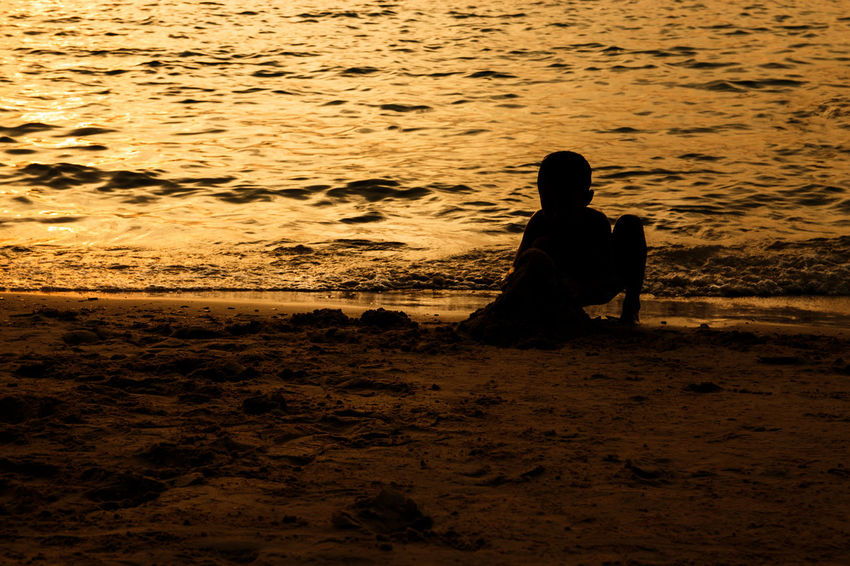 silhouette of people at the beach,The beauty of natural light at sunset. Sunset Real People Beach Sitting Land Water Sea Leisure Activity One Person Silhouette Nature Lifestyles Sky Holiday Men Vacations Beauty In Nature Trip Outdoors Hopelessness Silhouette Happiness Happy People Holiday Relaxing Children Women Man Romantic Orange Clouds And Sky Love Family Summer Sunrise Boy Freshair Freedom Fun