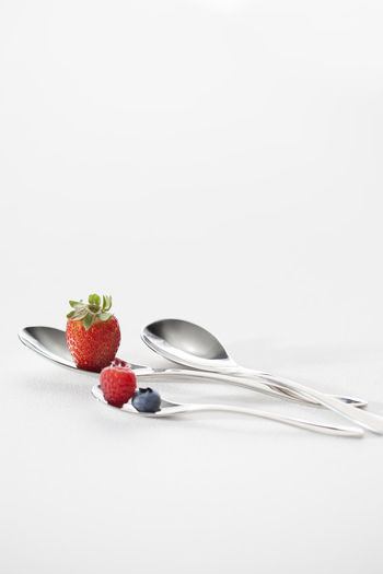 Fruits in bowl against white background