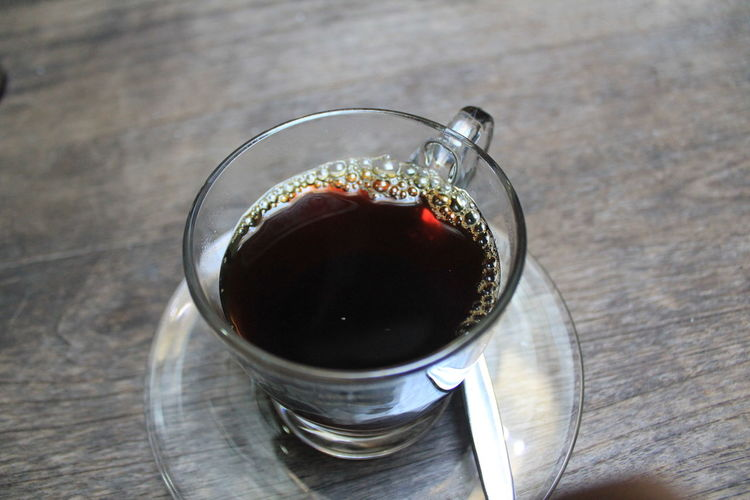 High Angle View Of Black Tea Served On Wooden Table