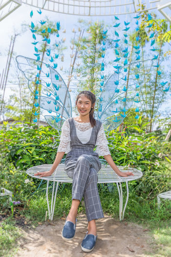 Full length portrait of smiling young woman sitting on butterfly structure against sky