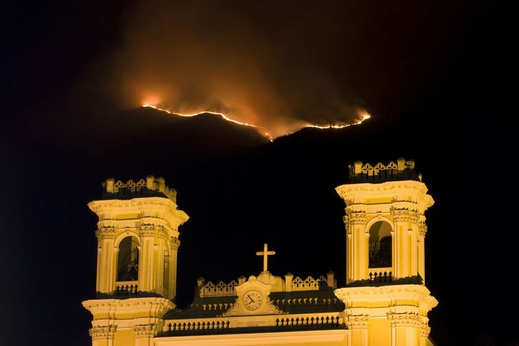 The church and the fire. A Fire on the Italian Alps with the Church of Cogollo del Cengio in foreground. Alps On Fire