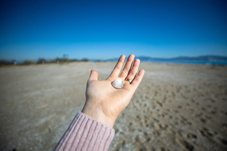 Midsection of person hand on land against sky