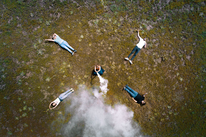 High angle view of woman with friends holding smoke bomb on field