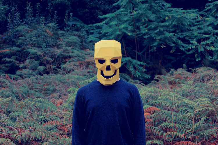 Close-Up Of Man Wearing Skull Mask Against Trees