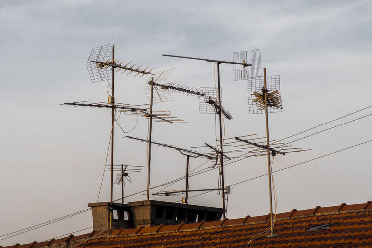 Low angle view of antennas against sky
