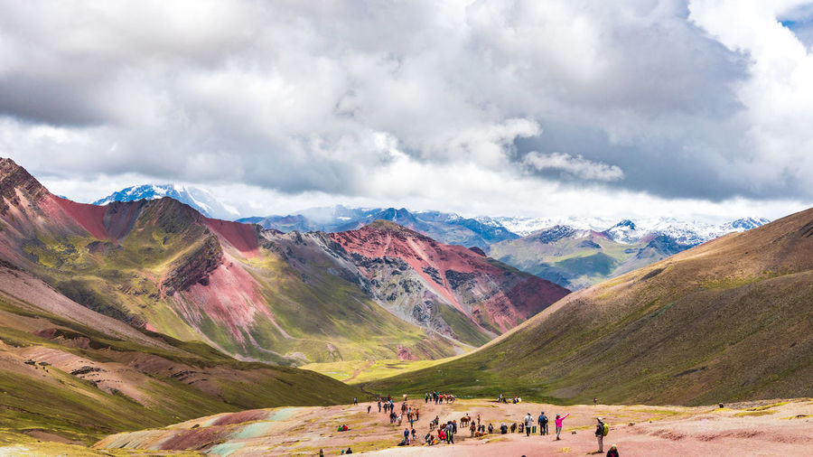 People on land against mountains and sky