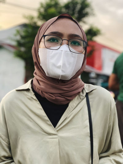 Close-up woman wearing mask standing outdoors
