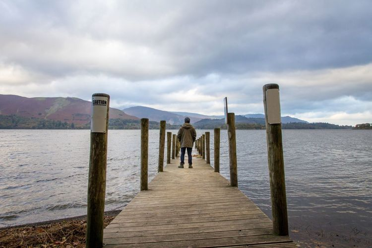 Rear view of mature man standing on pier over lake against cloudy sky