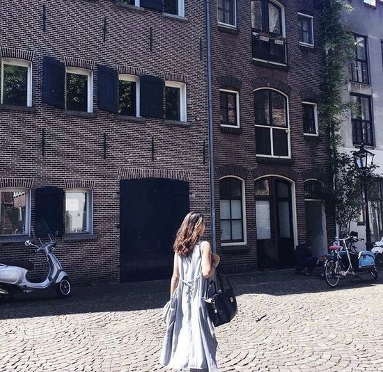 Woman standing against building in city