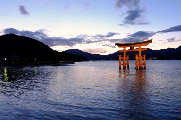 Itsukushima Shrine In Lake Against Sky During Sunset