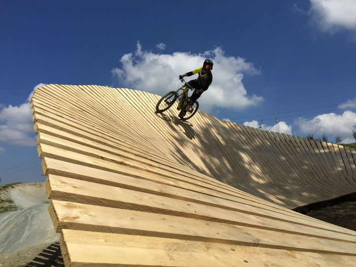 Low angle view of man riding mountainbike against sky