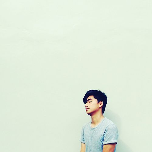 Young man leaning on wall