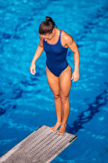 Female Diver Jumping Into The Pool Diving Diver Swimming Pool Woman Water Sport Training Competition Young Exercising Diving Board Board Above Action Swimwear Blue Activity Muscular Build Extreme Sports Caucasian Ethnicity Athlete Standing Jump Concentration