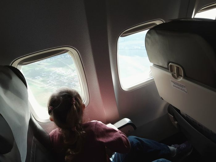 Rear view of a little girl sitting on an airplane looking out the porthole