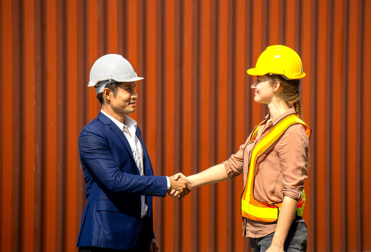 Colleagues wearing hardhat giving handshakes while standing against cargo container