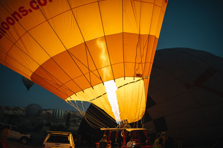 Hot Air Balloon Transportation Balloon Air Vehicle Yellow Group Of People Leisure Activity Real People Adventure Mode Of Transportation Nature Travel People Recreational Pursuit Ballooning Festival Burning Fire Outdoors Sky Inflating