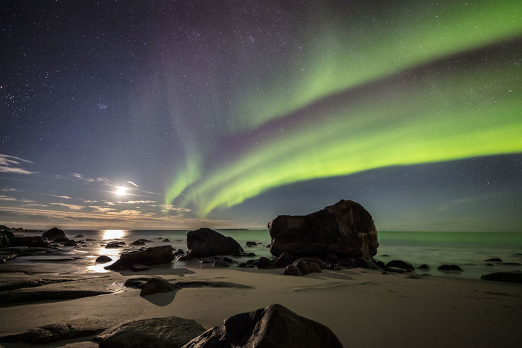 Scenic view of rocks at beach against aurora polaris in sky at night