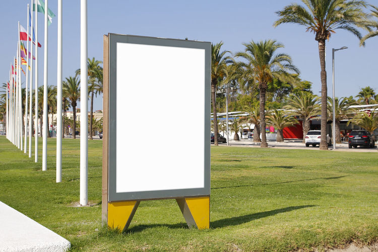 Blank billboard outdoors, in a public zone Billboard Advertising Poster Blank Banner White Mock Up Mockup Empty Street Tree Green Grass Palm Plants Eco Urban Outdoor Promo Promotion Building Background Media Mock Up Board Marketing Display Information Message Sign City Advertisement Outside Copy Commercial Public Panel Placard Ad Transportation Promo Promenade Car Park Parked Flag Mast Countries Flags