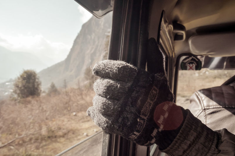 Hand wearing woolen gloves holding the door frame of a window. Beautiful young man sitting on the front passenger seats of a car along highway journey Enjoying travel. Winter holiday vacation concept Handle, Mode of Transport, Human Hand, Land Vehicle, Part Of, Driving, Chauffeur, Journey, Travel, Car, Traffic, Road Trip, Side-View Mirror, Vehicle Interior, Safety, Motor Vehicle, USA, Luxury, Inside Of, Looking Through Window, Drivers Point Of View, Travel vacation, Driveway, City Street, Transportation, Car Point of View, adult, adventure, auto, automobile, background, caucasian, freedom, fun, happy, holidays, lifestyle, outdoors, people, tourist, young, christmas, destination, leisure, season, sitting, tourism, trendy, winter, person Mountain Mode Of Transportation Transportation One Person Day Nature Sky Travel Winter Car Real People Land Vehicle Focus On Foreground Scenics - Nature Clothing Leisure Activity Lifestyles Motor Vehicle Cold Temperature Hand Outdoors Warm Clothing My Best Photo 17.62°