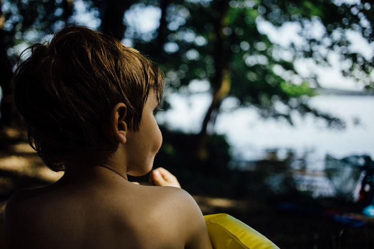 Rear view of shirtless boy at lakeshore