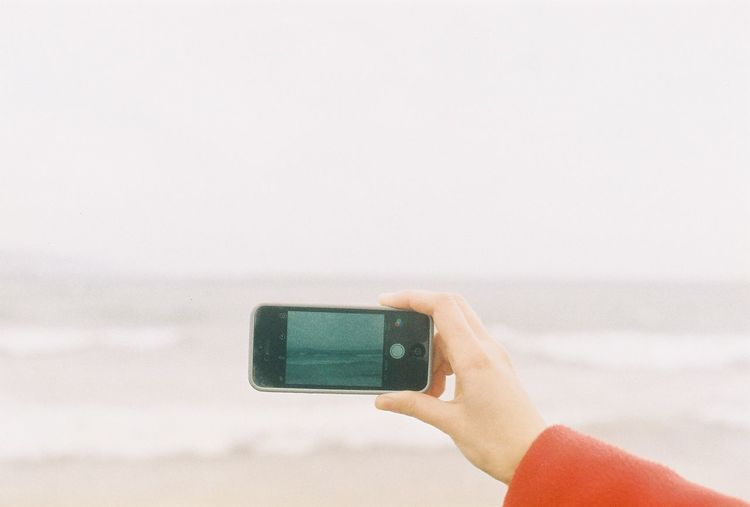 Hand photographing the sea with mobile phone