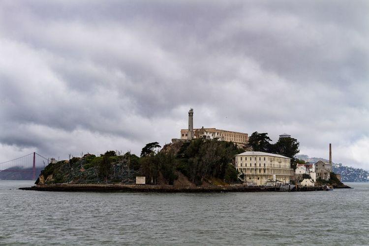 Buildings on island amidst sea against sky
