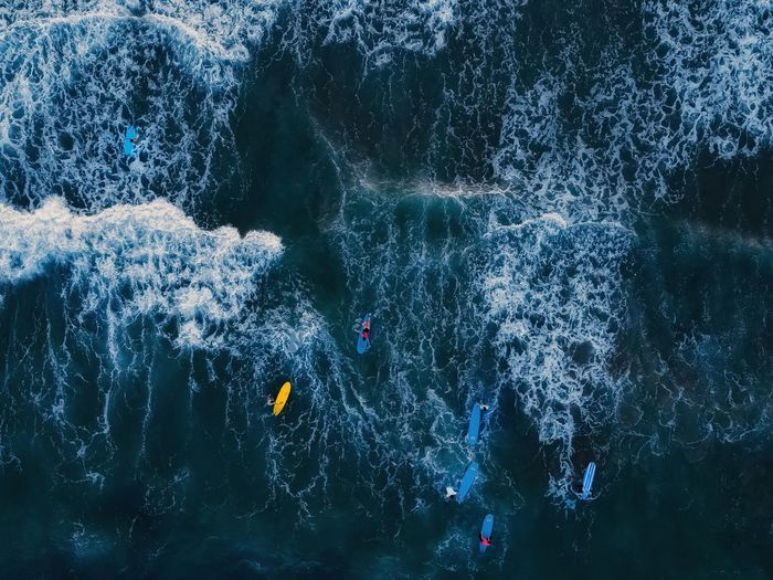 High angle view of people swimming and surfing in the sea