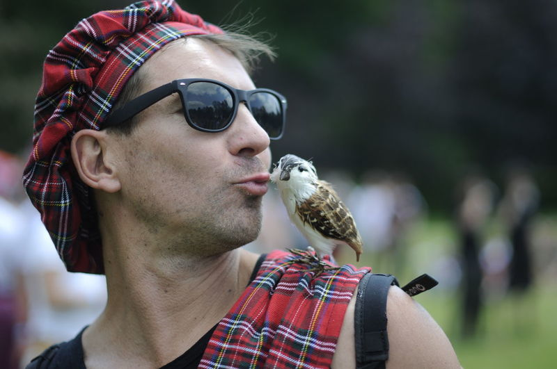 Close-up of mature man wearing sunglasses kissing bird sitting on shoulder